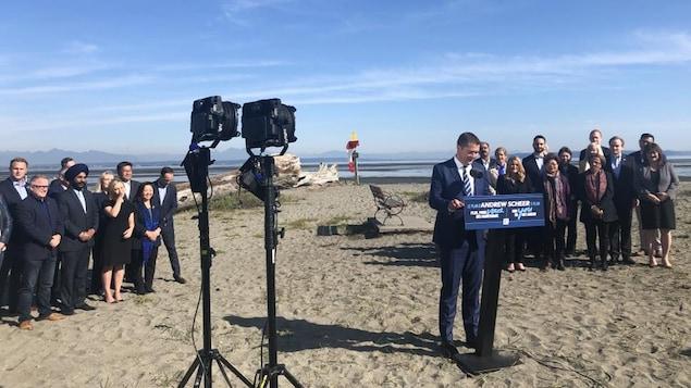Andrew Scheer fait une annonce sur une plage en compagnie d'une vingtaine de personnes. Derriere eux, il y a de l'eau et des montagnes.