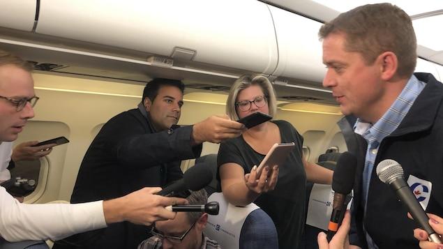 Andrew Scheer parle aux médias dans son avion de campagne.