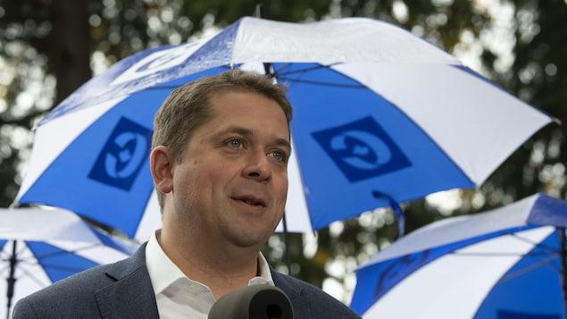 Andrew Scheer tient un point de presse sous la pluie. Derrière lui se trouve une rangée de parapluies.