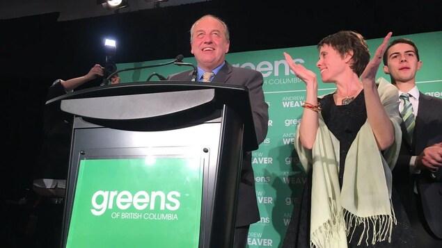 Andrew Weaver est acoudé à un pupitre sur une scène d'où il fait un discours. La députée verte Sonia Furstenau se tient à côté de lui et applaudit.