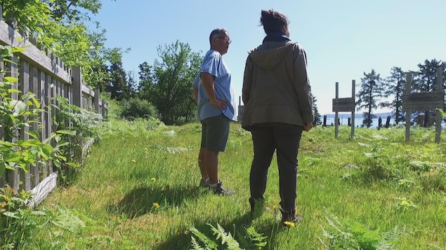 Andy Wilson et la journaliste se tiennent devant les stèles dans le cimetière.