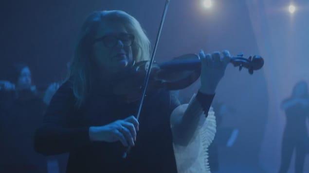 Une femme portant des lunettes et tenant un violon.