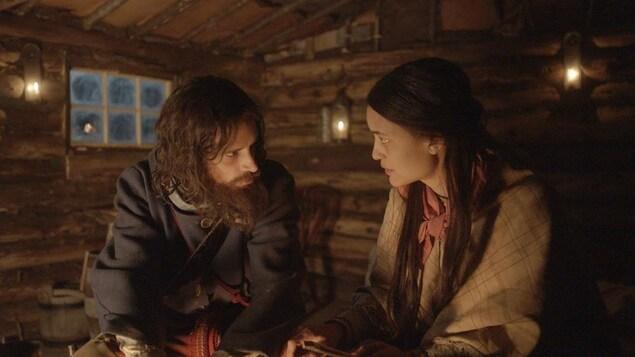 Une femme autochtone et un homme barbu se regardent dans les yeux dans une cabane de bois.