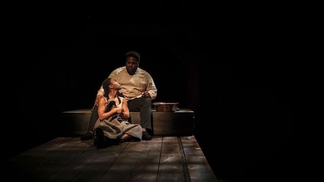 Une femme est assise devant un homme.