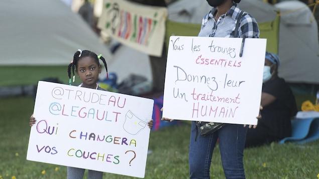 Une petite fille tient une pancarte sur laquelle il est écrit : « Trudeau, Legault, qui changera vos couches? »