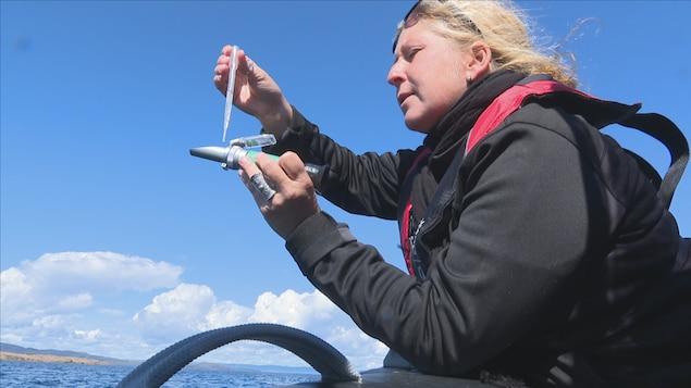 Une chercheuse en bateau utilise une pipette pour verser un liquide dans un instrument.