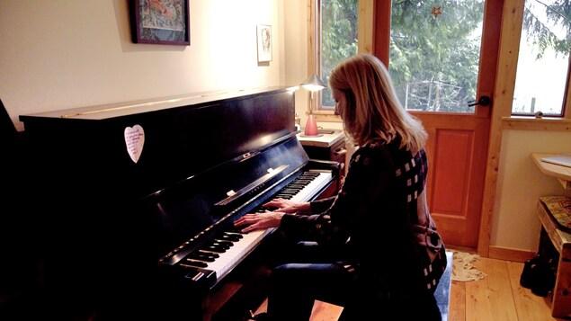 La musicienne Anna Lumière joue du piano dans sa petite maison sous les arbres.