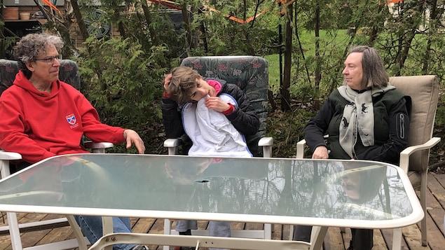 Yves, Anne et Lise sont assis à une table à l'extérieur.