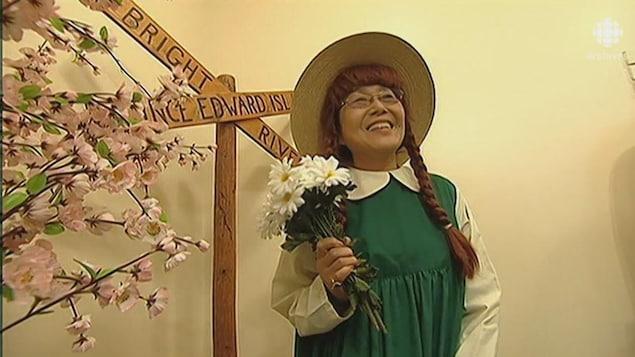 Touriste japonaise déguisée en Anne Shirley souriant à la caméra