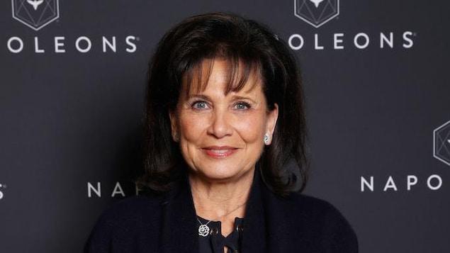 Une femme brune, habillée en noir, sourit.