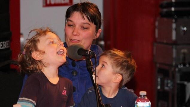 Anne Turbide devant un micro, accompagnée de deux enfants.