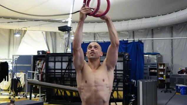 Photo de Yann Arnaud, artiste de cirque, qui tient des anneaux suspendus.