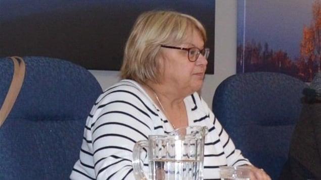 Une femme avec des lunettes assise.