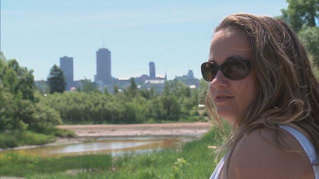 Une jeune femme avec, en arrière-plan, la silhouette de la Ville de Québec