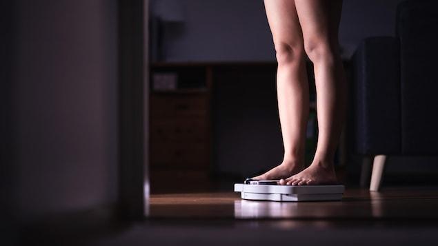 Une personne sur une balance, dans une pièce sombre. On ne voit que ses jambes.