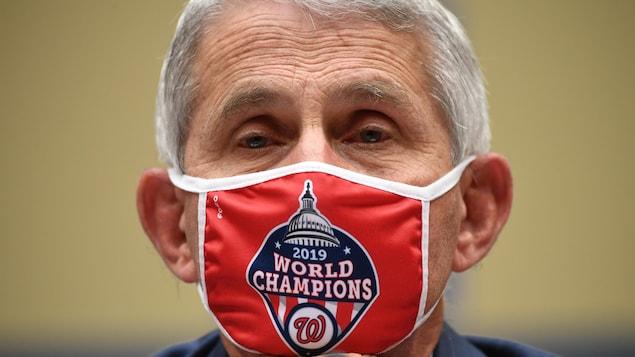 Gros plan du Dr Fauci qui porte un masque où il est inscrit: World Champion