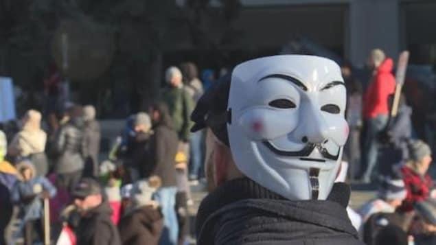 Un homme porte le masque de Guy Fawkes qui est de couleur blanche avec des sourcils et une moustache finement dessinés.