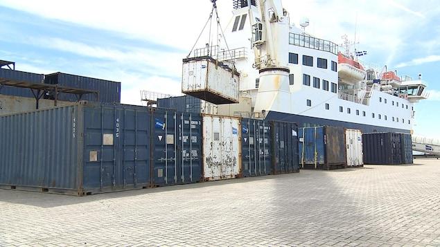 La grue décharge des conteneurs du navire Bella-Desgagné vers le quai de Port-Menier sur l'île d'Anticosti, on aperçoit aussi derrière la passerelle pour les passagers.