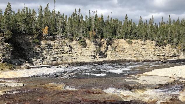 La rivière s'écoule, bordée de caps rocheux.