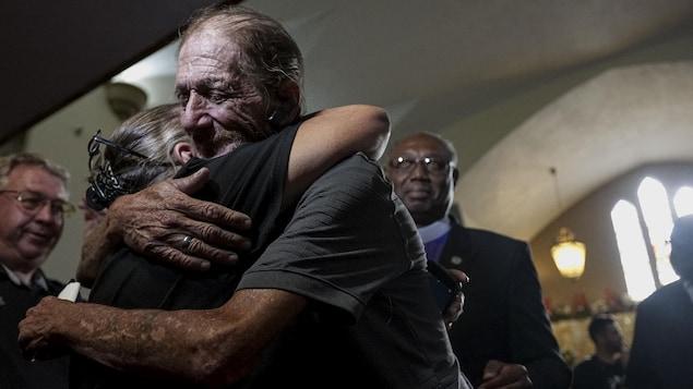 Un homme, visiblement ému, serre dans ses bras une femme dans une église.