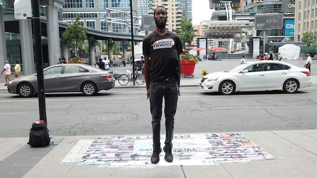 Un jeune homme saute à pieds joints devant la place Yonge-Dundas de Toronto.