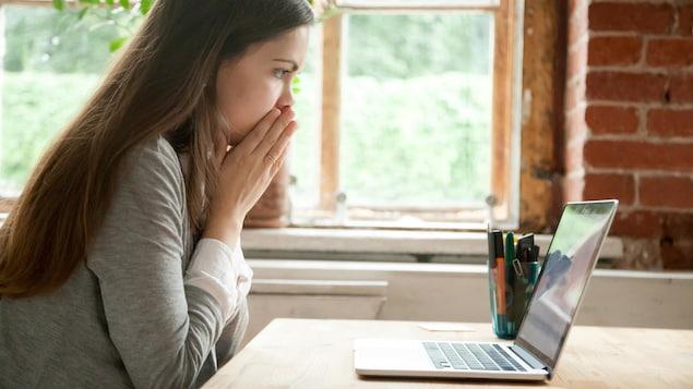 Une jeune femme semble inquiète et met les mains devant sa bouche en regardant l'écran de son ordinateur.