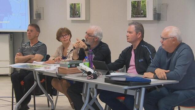 Cinq membres de l'APLK dirigent la rencontre à l'avant de la salle.