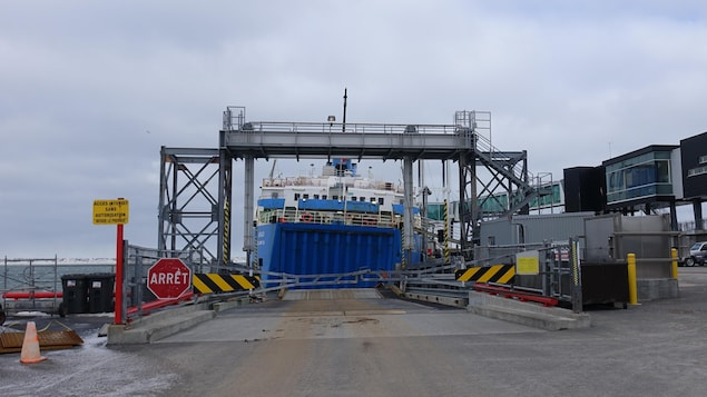 Au quai de Matane, la barrière menant au traversier est fermée. Vu de derrière, le navire penche légèrement vers la droite.