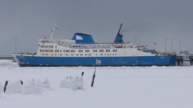 On voit un gros navire sur le fleuve Saint-Laurent. Il est entouré de neige. Il s'agit du traversier Apollo.