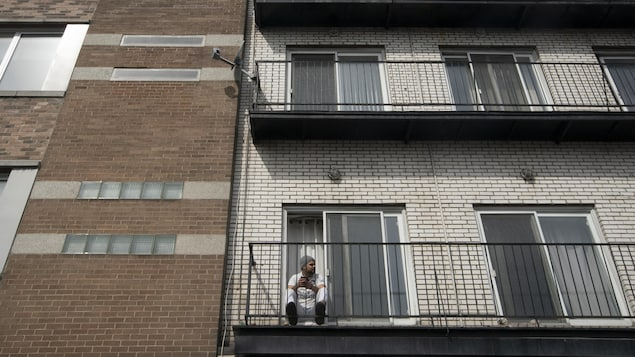 Un homme seul sur son balcon.