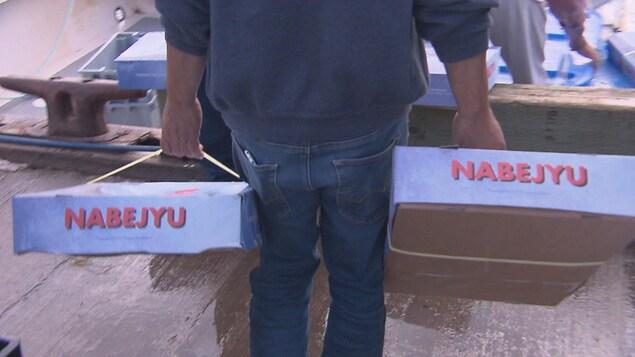 Un homme transporte des boîtes de poisson.