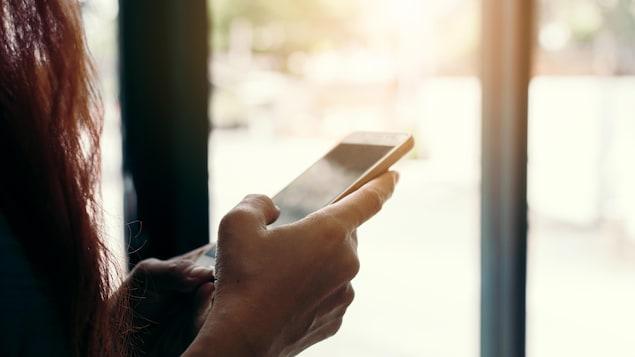 Une femme consulte son téléphone cellulaire.
