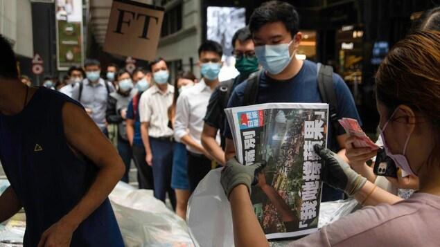 Une femme tient une pile de journaux. Devant elle, une dizaine de personnes attendent en file.