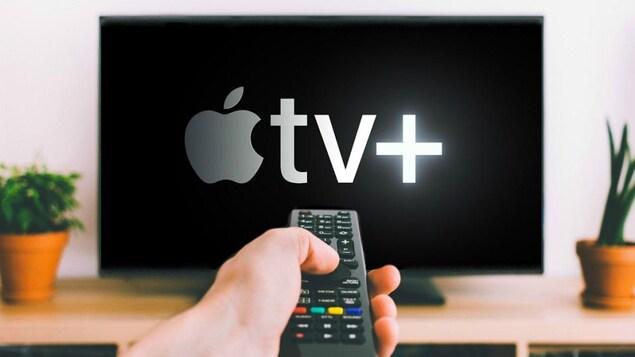Une main tient une manette devant un écran de télévision qui affiche le logo de la plateforme Apple TV+.