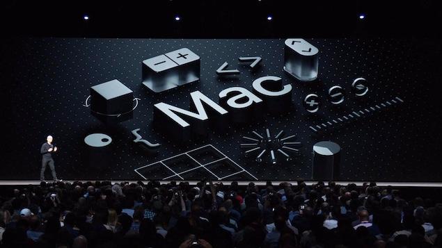 Une capture d'écran de la présentation d'Apple montrant Tim Cook sur la scène d'un amphithéâtre avec le mot «Mac» affiché à l'écran derrière lui.