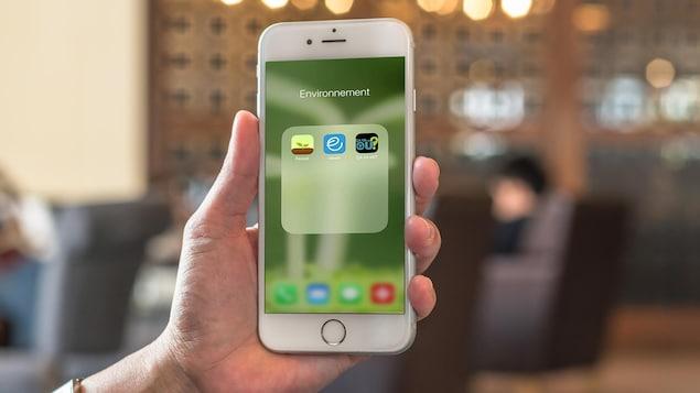 Trois applis écolo sur un écran de iPhone dans un café.