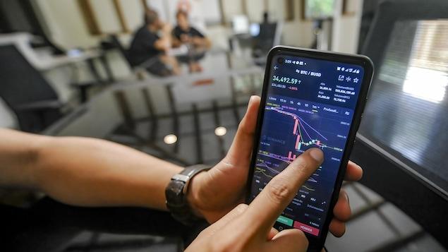 Un homme tient un téléphone cellulaire affichant une application qui indique le prix du bitcoin.