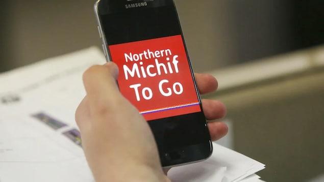 Un téléphone tenu dans une main, qui affiche l'inscription Northern Michif To Go en blanc sur fond rouge.