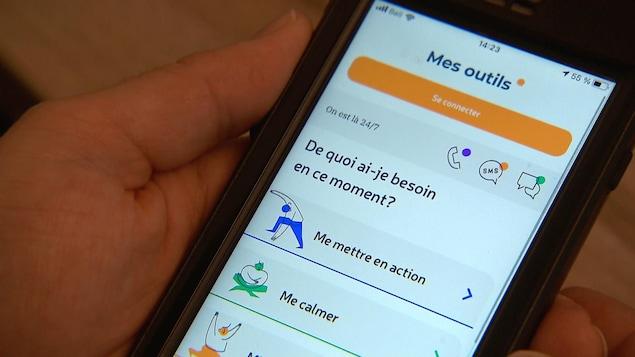 Un téléphone intelligent dans une main. On voit une application sur le bien-être ouvert, avec des thèmes comme Me mettre en action et me calmer.