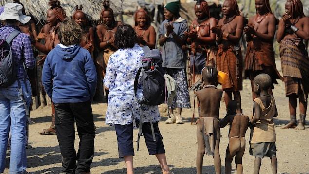 Des touristes assistent à une danse de femmes dans un petit village de Namibie.