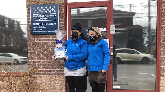 Deux femmes se trouvent devant le bureau du député de Dubuc, François Tremblay.  Elles portent un panier.