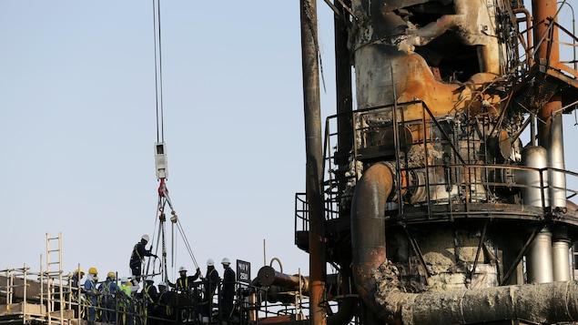 Des travailleurs montent dans une nacelle au site pétrolier de Saudi Arama, endommagé à la suite de l'attaque.