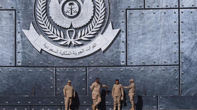 Des officiers de l'armée saoudienne discutent dans la capitale, Riyad. Derrière eux, on peut voir un logo des forces nationales de l'Arabie saoudite.