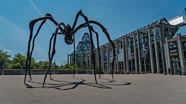 Une sculpture d'araignée en fer forgé devant un musée