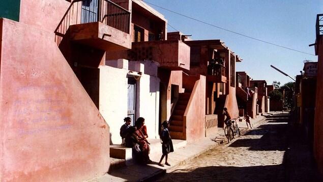 Des enfants jouent dans la rue à Indore, en Inde, devant des maisons à un étage de couleur ocre.
