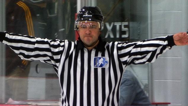 Un arbitre effectue un signe avec les bras.