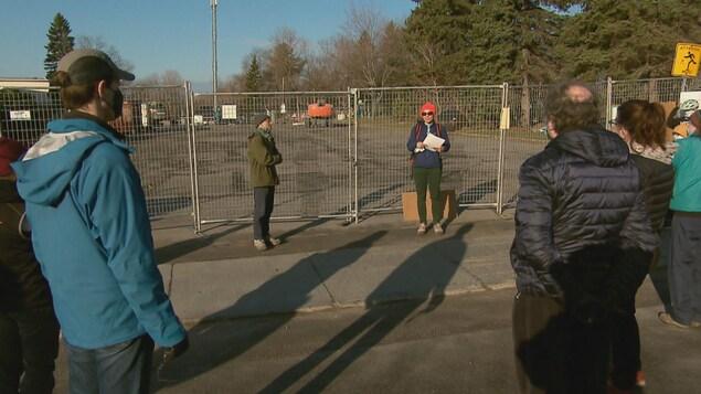 Des gens sont rassemblés près d'un emplacement clôturé.