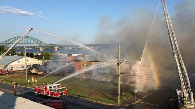 Une photo prise de haut de la municipalité de Miramichi au Nouveau-Brunswick. Des pompiers sont au prise avec une incendie au théâtre Vogue et un arc-en-ciel est créée par le contraste entre le temps chaud et l'eau projetée par les équipes.