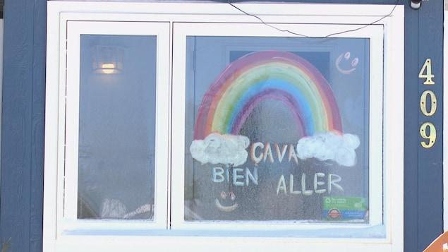 Un arc-en-ciel et l'inscription ça va bien aller sont apposés sur la fenêtre de Transit Sept-Îles.