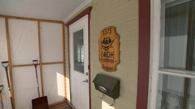 Une porte blanche, à côté on voit une enseigne sur laquelle il est écrit L'Arche le printemps, bureau.